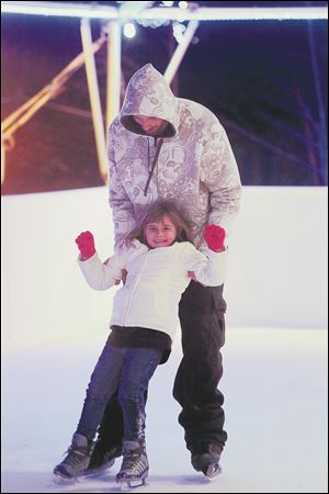 Mike Mayhugh, of South Toledo, holds up his daughter Mackenzie, 7, as the pair skate.