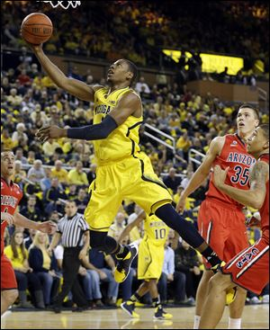 Michigan forward Glenn Robinson III makes a layup as Arizona center Kaleb Tarczewski (35) looks on during the first half Saturday in Ann Arbor, Mich.