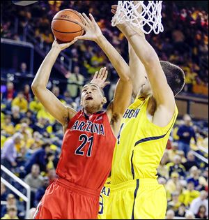 Arizona forward Brandon Ashley (21) makes a layup while being defended by Michigan forward Mitch McGary during the second half. Ashley had 18 points for the Wildcats as they held off Michigan.