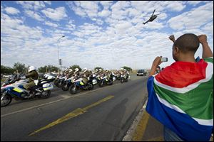 A child draped in the South African national flag gestures while taking a photo of the procession as the body of former president, Nelson Mandela arrives at the Waterkloof Air force base in Pretoria. From there it will be transported to Qunu for a state funeral on Sunday.