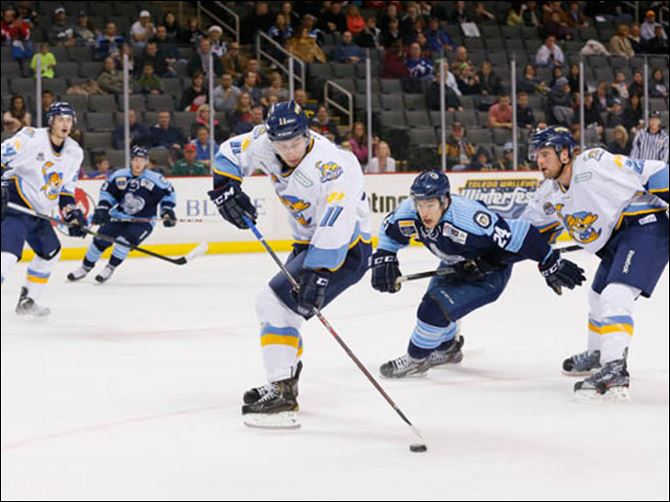 SPT Walleye15p Toledo Walleye player Scott Arnold (11) picks up a loose puck against the Evansville IceMen during the second period.