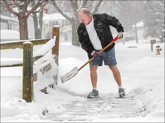 15n1shorts-2 Ken Dreeze shovels his sidewalk in Maumee — in shorts. After all, winter is still a week away.  Temperatures though will remain in the mid-20s today, and 30 mph winds are expected.