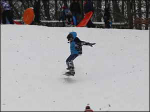 Bailey Davis, 12, of Toledo snowboards down at the Sledding Hill in Pearson Metropark in Oregon.
