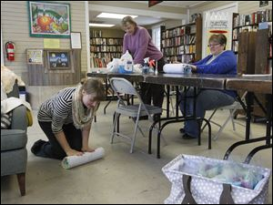 Sara Box, left, gets on the floor to roll her felt and silk material that is around a styrofoam noodle in one of the last steps to make a  felted silk scarf. Students Gail McCain, center, of Perrysburg, and Debbie Thompson of Bowling Green watch as they roll their own hand made scarves.