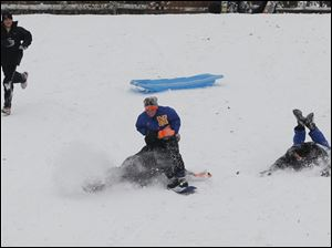Dominik Bernejo, 16, tackles Ty Zieroff, 11, as Zieroff tries to snowboard down the hill at Pearson Metropark in Oregon. At left is Austin Cole, 12; at far right is Jacob Zieroff, 16. They are all from Northwood.