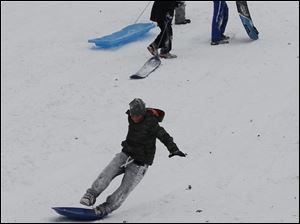 Erik Marazon, 12, of Northwood rides a sled standing up at the Sledding Hill in Pearson Metropark in Oregon.