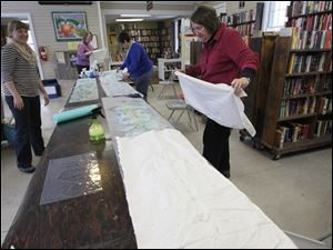 Sara Box, left, shows students from left: Gail McCain of Perrysburg, Debbie Thompson of Bowling Green, and Christine Onasch of Bowling Green how to cover their felt and silk with material before rolling it to make a felted silk scarf.