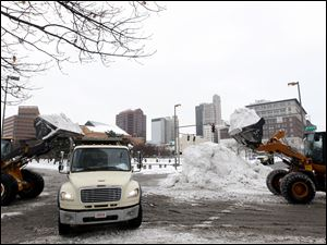 City of Toledo Sewer and Drainage trucks haul away snow that they collected after clearing Jackson and N. Huron.