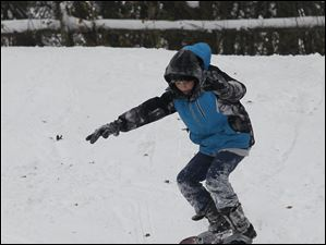 Bailey Davis, 12, of Toledo snowboards down the hill. Sledders take advantage of the record snowfall at the Sledding Hill in Pearson Metropark in Oregon.