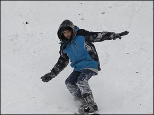 Bailey Davis, 12, of Toledo snowboards at Pearson Metropark.