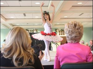 Nutcracker dancer Gwenivere Durand, 12, strikes a pose on the runway at the Flower Hospital Holly and Ivy Fashion Show.