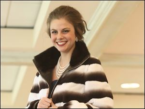 Miss Teen Michigan, Alana Wilson, 17, models a fur coat over a floor-length gown at the Flower Hospital Holly and Ivy Fashion Show at the Inverness Club in West Toledo.
