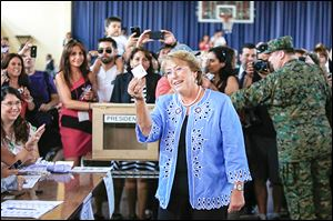 Former President Michelle Bachelet, who left office in  2010 with an approval rating of 84 percent, holds up her vote before casting it in Santiago on Sunday.