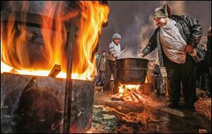 Activists cook meals during a rally in the Independence Square in Kiev, Ukraine. About 200,000 anti-government demonstrators converged on the central square of Ukraine's capital on Sunday. U.S. Sen. John McCain (R., Ariz.) spoke to the crowd.