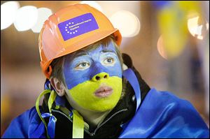 Pro-E.U. activist Andriy Zavodyuk shows Ukraine's national flag's colors on his face at a rally in Kiev.