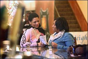 Toni Battle, left, a health-care navigator with the Neighborhood Health Association, talks with Leslie Hayward of West Toledo at Our Brothers Place in downtown Toledo. Outreach workers visit various forums to sign up uninsured people before Dec. 23.