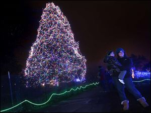 Courtney Kihlken, of Marblehead, right, holds her nephew Mason Kihlken, 3, as they pose for a photograph by a lit pine tree during this year's Lights Before Christmas at the Toledo Zoo.