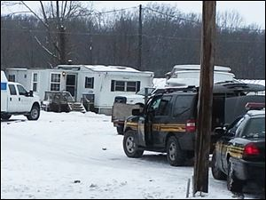 Wayne County sheriff's deputies secure the scene while investigators from the Ohio Bureau of Investigation search a mobile home in Wayne County's Green Township on Sunday.