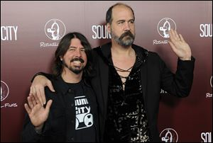 "Dave Grohl, left, poses with Nirvana bandmate Krist Novoselic at the premiere of the documentary film ""Sound City,"" in Los Angeles in January."