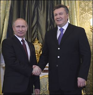 Russian President Vladimir Putin, left, shakes hands with his Ukrainian counterpart Viktor Yanukovych during their meeting in Moscow today.