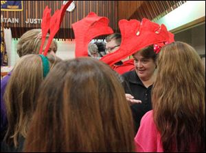 Beth Schwandt, center, operations manager with the Salvation Army, instructs Penta volunteers, who are wearing reindeer ears, how to help families
