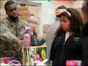 Sgt. Yves Jospeh, with the Weapons Company 124th, Perrysburg, OH, left, and volunteer Taylor Boggs, right, help a client choose between two dolls.