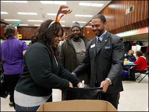 Penta volunteer Melinda Wells, left, bags toys with the help of Dr. Romules Durant, TPS superintendent, right, for Mark Hicks Sr. , center, and his family.