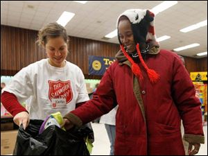 Volunteer Kaitlin Wasik, left, helps Rakesha Grice, right, from Toledo, pick out hats for her children.