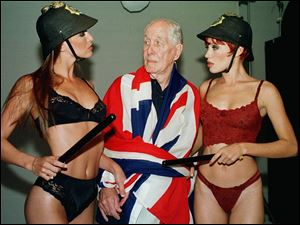 This Jan. 25, 2001 file photo shows Ronnie Biggs, one of Britain's most notorious criminals, wrapped in a Union Jack flag, posing for photos with lingerie models Milene Zardo, left, and Francine Mello.