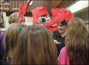 At right, Beth Schwandt, operations manager for the Salvation Army, instructs Penta volunteers — who are wearing reindeer ears — on how to help families at the giveaway.