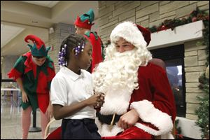 Laquantis Coker, a first grader at Rosary Cathedral tells Santa (Adam Hock) what she wants for Christmas during  St. John's Jesuit Jesuit High School & Academy's 15th annual Christmas on Campus on Dec. 4.