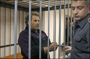 A police officer guards the U.S. captain of the Greenpeace ship 'Arctic Sunrise', Peter Willcox in a cage in a court room in Murmansk, Russia in September.