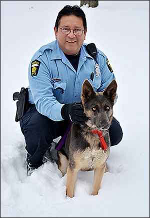 Toledo police Officer Dave Avalos with Dakota, a stray shepherd that he took in after having found her in an empty lot.