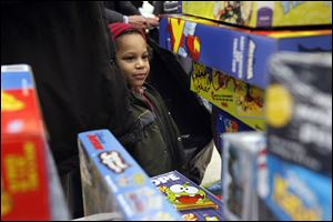 Da'Von Hicks, 4, gazes at a pile of games, above, during the Salvation Army's annual Christmas distribution at the United Auto Workers Local 12 hall.  Families who applied and were approved in October and November collected toys Wednesday  for their children, as well as a holiday food basket.