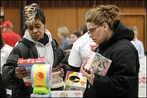 Vivian Myers, left, and Victoria Pasco sort through toys.