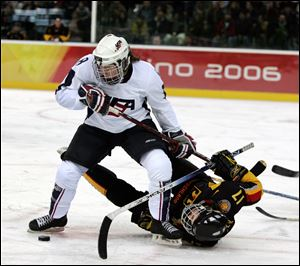 United States' Caitlin Cahow (8) upends Germany's Sara Seiler during the first period of a 2006 Winter Olympics ice hockey match in Turin, Italy. Cahow will join Deputy Secretary of State Bill Burns at the closing ceremony delegation of the Winter Olympics next year in Sochi, Russia.