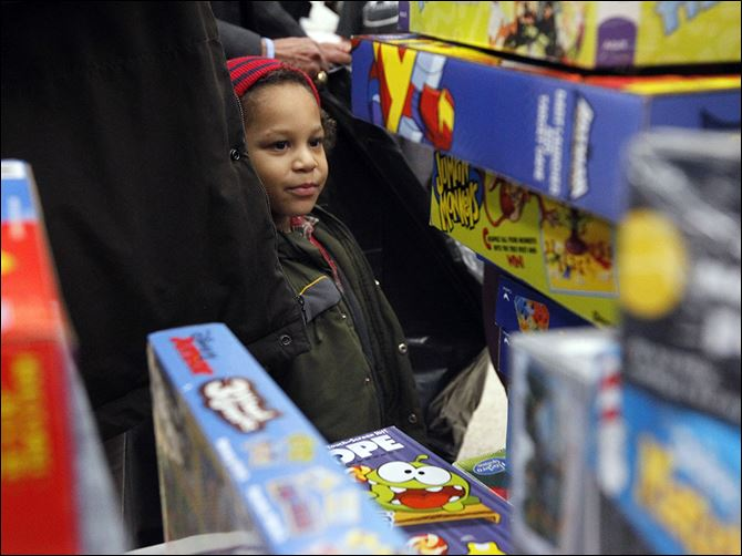 n5giveaway-2 Da'Von Hicks, 4, gazes at a pile of games, above, during the Salvation Army's annual Christmas distribution at the United Auto Workers Local 12 hall.  Families who applied and were approved in October and November collected toys Wednesday  for their children, as well as a holiday food basket.