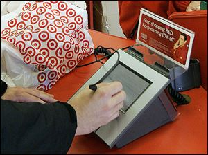 A customer uses a credit card at a Target store. The breach does not affect online purchases.