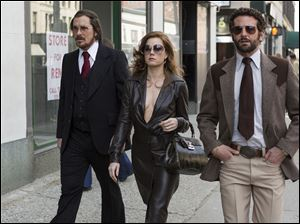 "Christian Bale, left, as Irving Rosenfeld, Amy Adams as Sydney Prosser, and Bradley Cooper as Richie Dimaso walking down Lexington Avenue in a scene from Columbia Pictures' film, ""American Hustle."""