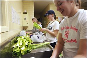 Natalie Walter, 16, Erin Schaefer, 17, and Emily Currier, 16, from left, share a laugh while washing celery to be used in the dishes to be taken to Kentucky.