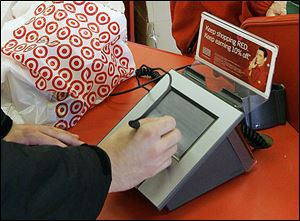 A customer signs his credit-card receipt at a Target store in Florida. Target was among the retailers that had their customers' data breached last year.