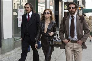 Christian Bale, left, as Irving Rosenfeld, Amy Adams as Sydney Prosser, and Bradley Cooper as Richie Dimaso walking down Lexington Avenue in a scene from Columbia Pictures' film,