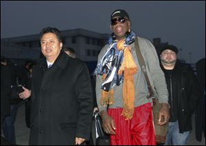 Former NBA basketball star Dennis Rodman walks with Vice Minister of North Korea's Sports Ministry, Son Kwang Ho, as Rodman arrives at the international airport in Pyongyang, North Korea today.