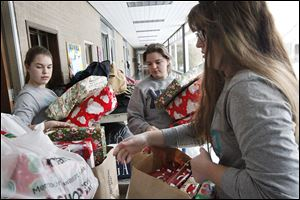 Carra Gilson, 16, Calla Gilson, 18, and Maggie Burlingame, 18, from left, gather Christmas presents in the kitchen of Notre Dame Academy in Toledo to load into a storage container during final preparations for the school's Christmas in Appalachia Celebration in Harlan, Ky.