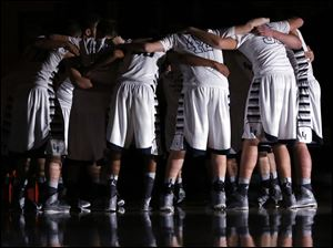 The Lake High School basketball team huddles before the game.