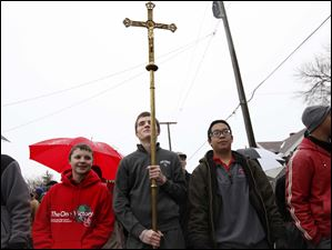 Head Server Tony Mossing, 17, center left, holds the crucifix aloft as he and his fellow servers, Jonathon Hrifko, 15, left, Sam Meier, 16, center right, and Connor Biddle, 17, right, lead the procession.