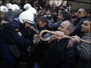 Farmers clash with riot police outside Greece's parliament in Athens on today.