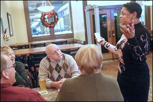 Toni Battle, a health-care navigator with the Neighborhood Health Association, speaks with Port Clinton residents Scott Jones, left, Judy Allen, Bob Allen, and Terri Jones at Our Brothers Place in downtown Toledo during a recent forum. A public sign-up will be held from noon to 7 p.m. Monday at the downtown library.