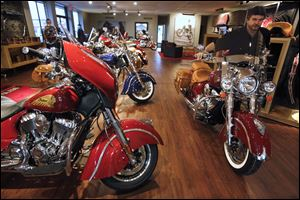 Sales specialist Jeff Eckman pushes an Indian Chieftain motorcycle through the showroom at the new Indian Motorcycles dealership, part of the Honda East Toledo dealership but in a separate building on Conant Street in Maumee. The first Indian arrived in the showroom on Nov. 1.