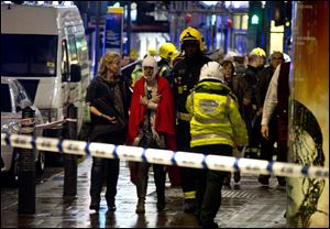 A woman stands bandaged and wearing a blanket  given by emergency services  following an incident at the Apollo Theatre, in London's Shaftesbury Avenue, Thursday evening.